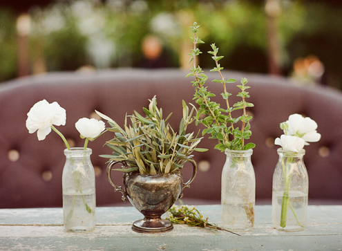 Herbs and flowers in milk bottles decor by OnceWed.
