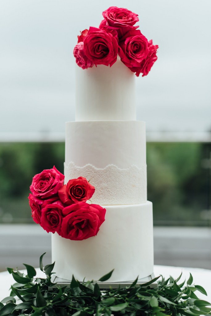 three tier white wedding cake with pink flowers on greenery bedding