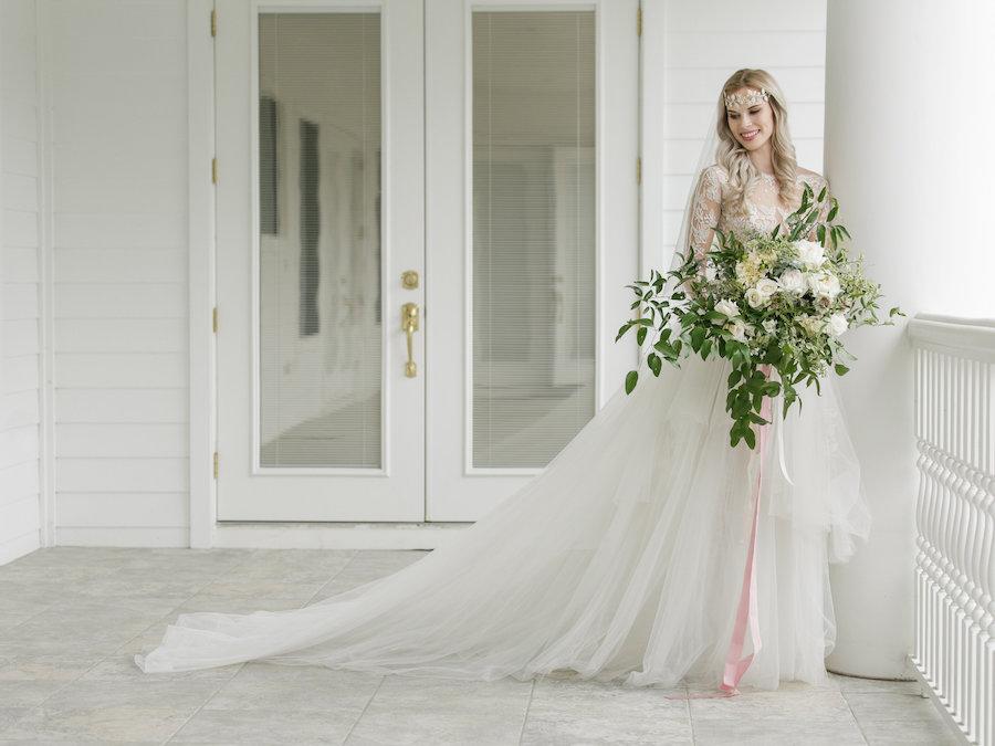 glamorous wedding dress with lush greenery bouquet