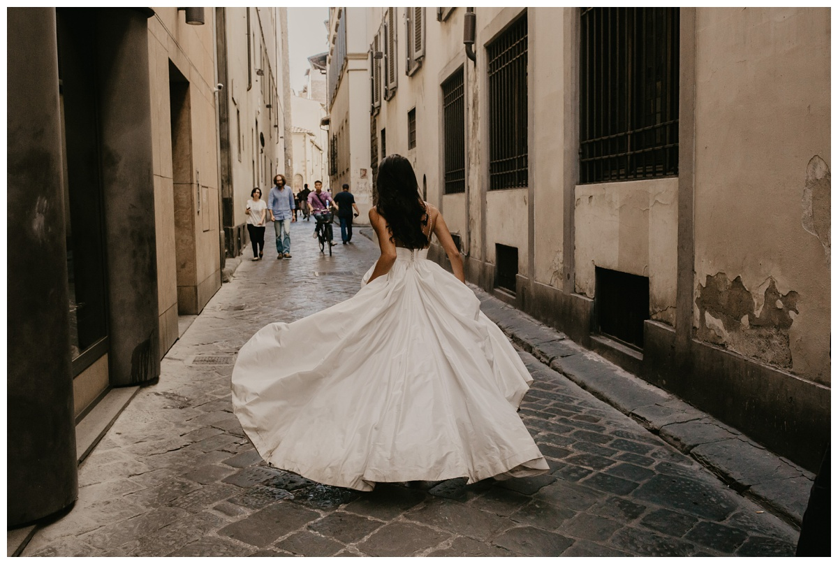 bride running and holding dress available in half sizes ensuring the perfect fit with people coming towards her on cobblestone streets lined with old stucco buildings