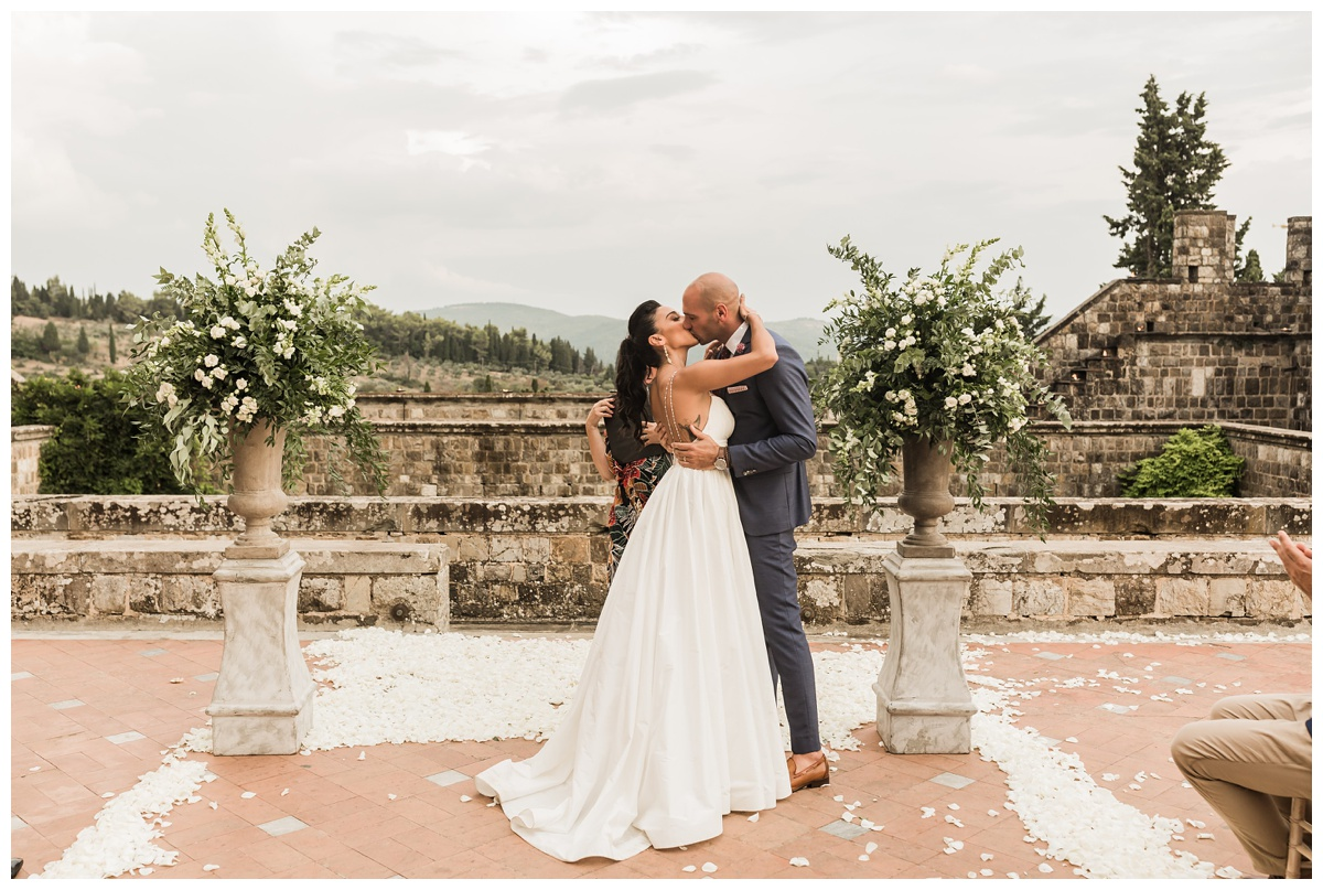 couple kissing at intimate tuscan wedding in italy at end of wedding ceremony with rose petals on ground. bride is wearing eco friendly wedding dress that is both classic and timeless