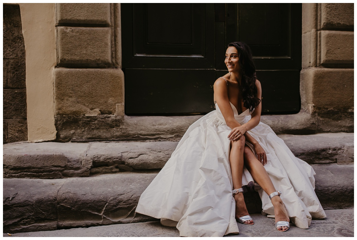 bride sitting on steps at intimate tuscan wedding wearing customized lea ann belter wedding dress available in half sizes ensuring the perfect fit and smiling