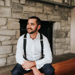 Groom sits in front of the venue's fireplace as he gets ready in his white button up and suspenders before the ceremony.