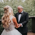 Bride wears Hayley Paige wedding dress for first look moment with her father who is holding his daughter's hands.