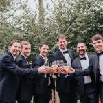 Five groomsmen and the groom gather together for a toast.