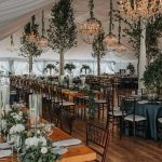 Magical Vermont destination wedding reception tent filled with long wooden farmhouse tables for guests and hanging chandeliers and greenery.
