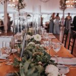 Long wooden wedding reception table draped with runner of fresh greenery.