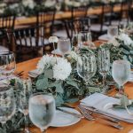 Farmhouse wedding table with greenery running down the center of the long table and white floral accents placed among the greens.