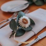Individual flower sits on folded white napkin at each place setting.