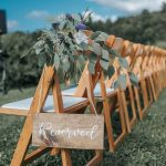 Upclose view of reserved sign hanging on a row of wooden folding chairs outdoor at the wedding ceremony.