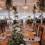 Looking down the long cedar farmhouse reception tables under the tent decorated with hanging chandeliers, twinkle lights, and greenery.