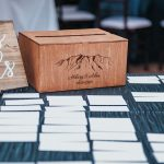 Wooden card box with mountain design sits on reception table next to seating cards.