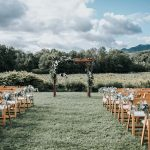 Looking down the aisle of outdoor Vermont wedding ceremony with wooden folding chairs on either side of the aisle and a wooden overhang covered in greenery for the ceremony.