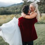 Groom wears red velour suit jacket and scoops his bride off the ground in a Vermont field at Topnotch Resort