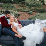 Bride lays out on outdoor couch with her back against the groom who is wearing a velour suit jacket