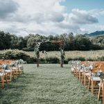 View down the aisle of wedding ceremony set-up with folding chairs on either side of the aisle and an archway at the end of the aisle in front of the trees and blue sky in the distance.