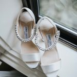White Jimmy Choo heels with sparkling ankle straps sit on window ledge