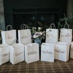 Bridesmaids gift bags with custom calligraphy on the front lined up around floral bouquet.