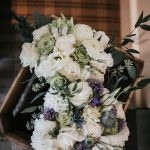 Bridesmaid bouquet of white and green flowers sits on top of bridal bouquet of white and purple flowers.