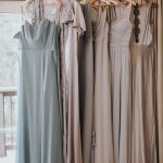 Pastel BHLDN bridesmaids dresses in blue, purple and gray hang next to each other in front of window
